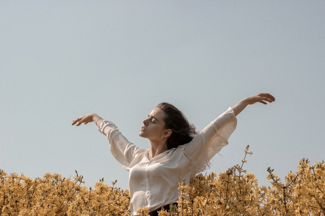 A beautiful careless woman experiencing the zen of perfect time management skills in the open space.